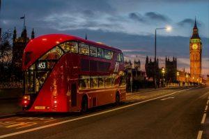 Red doubel decker bus passing in front of Big Ben