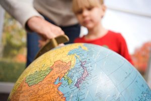 child being shown a picture of the globe