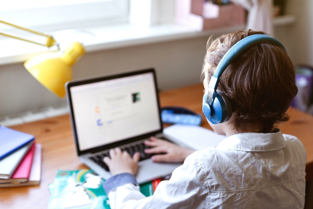 Child working on a computer with headphones