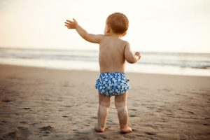 Baby standing on a beach with sandy legs in a reusable swim diaper