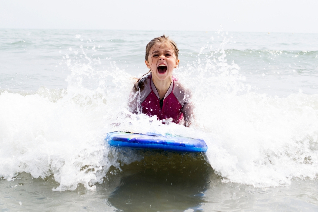child on a boogie board wearing a wetsuit