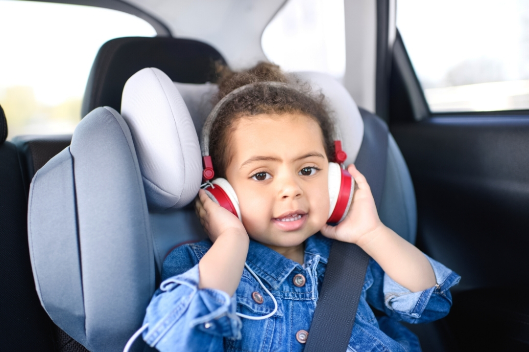 Toddler in a car seat with a set of headphones