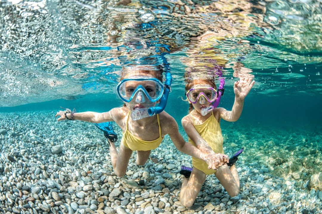 two girls swimming underwater in the ocean waving at a camera