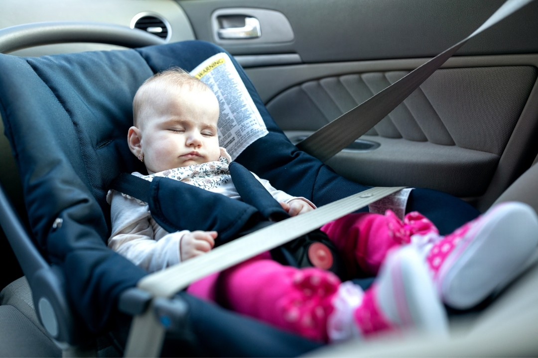 baby sleeping in a car seat - road trip tips for a baby
