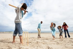 Family playing crciket on the beach - beach games for families