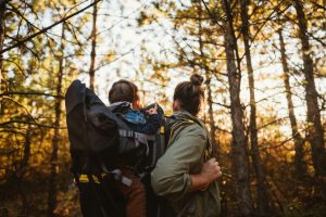 woman in the forest with a baby on her back in a hiking bakcpakc
