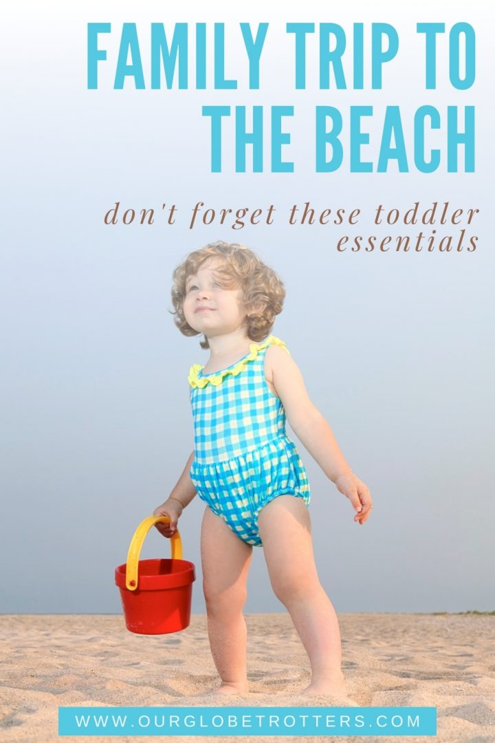 toddler girl holding a beach bucket - family trip to the beach toddler essentials