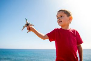 4 year old child holding a toy airplane