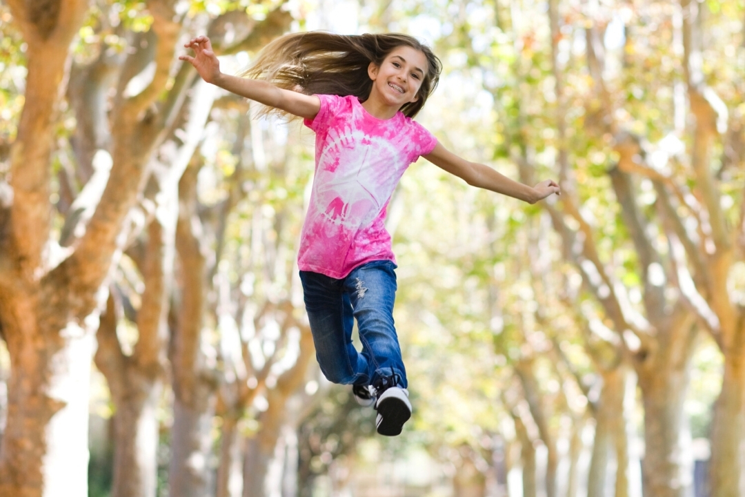 Tween pre-pubescent child jumping for joy through trees