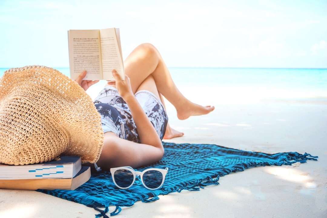 Lady relaxing on a beach mat reading a book