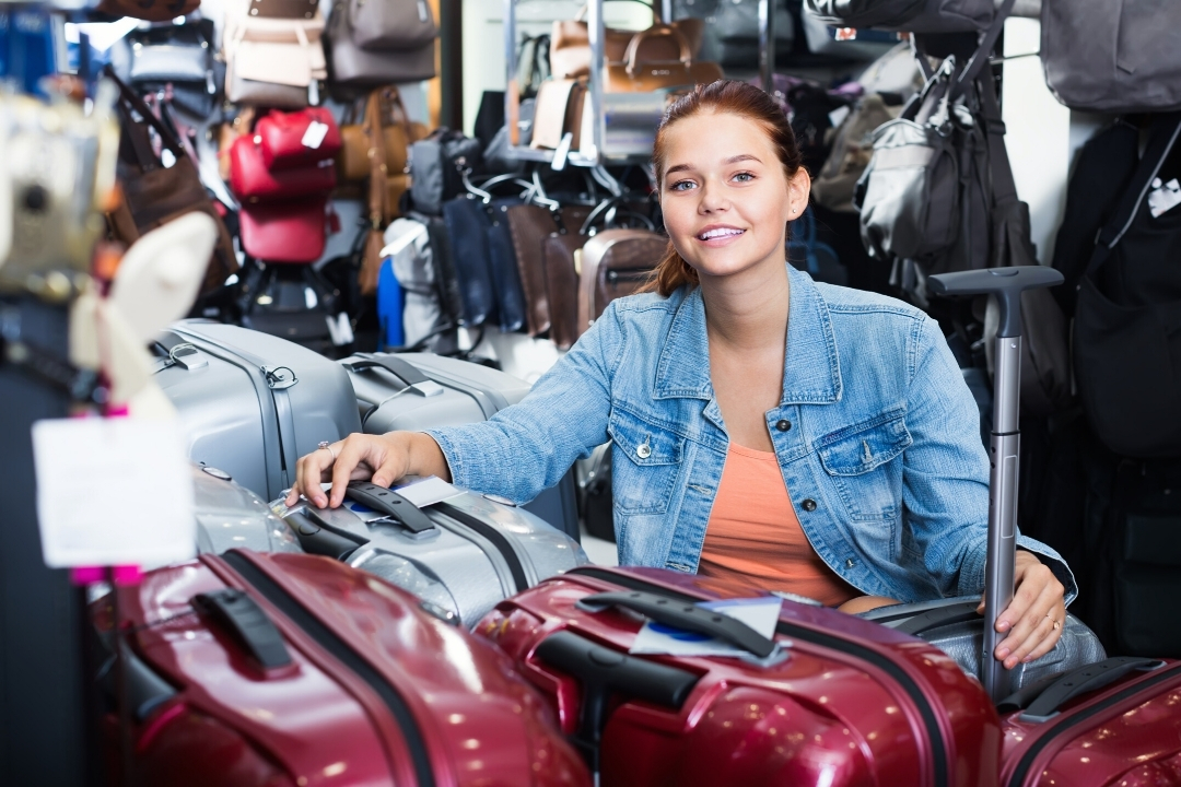 Teenage girl with red suitcases in a luggage store