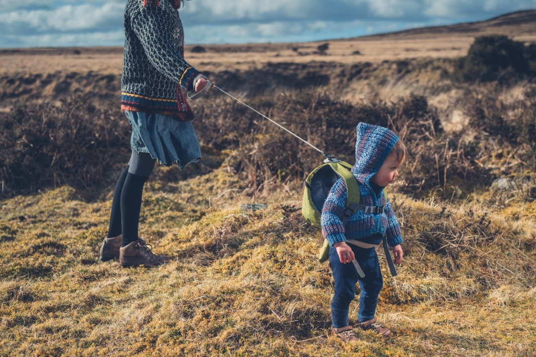 Toddler in winter wear with a toddler backpack harness with tether