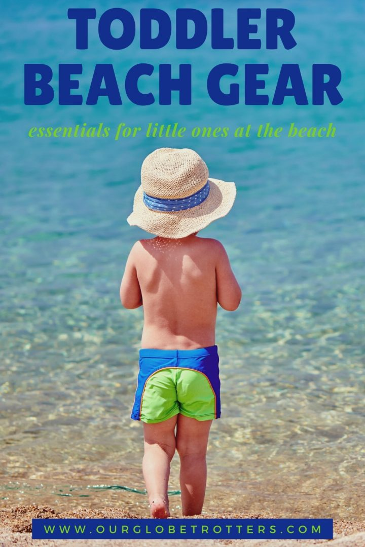 back of a toddler boy in swim shorts tanding on a beach with a sun hat - caption toddler beach gear