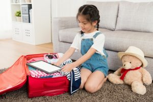 Young smiling girl packing a suitcase on the floor