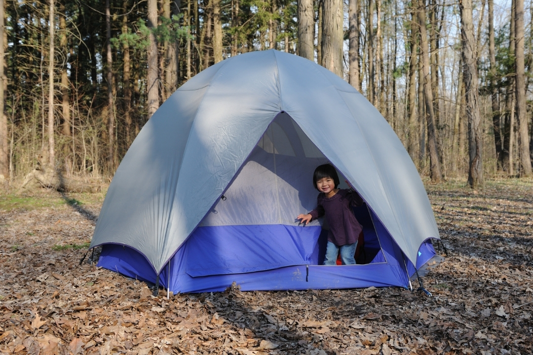 toddler climbing out a tent camping