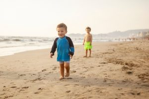 two toddler boys on a beach