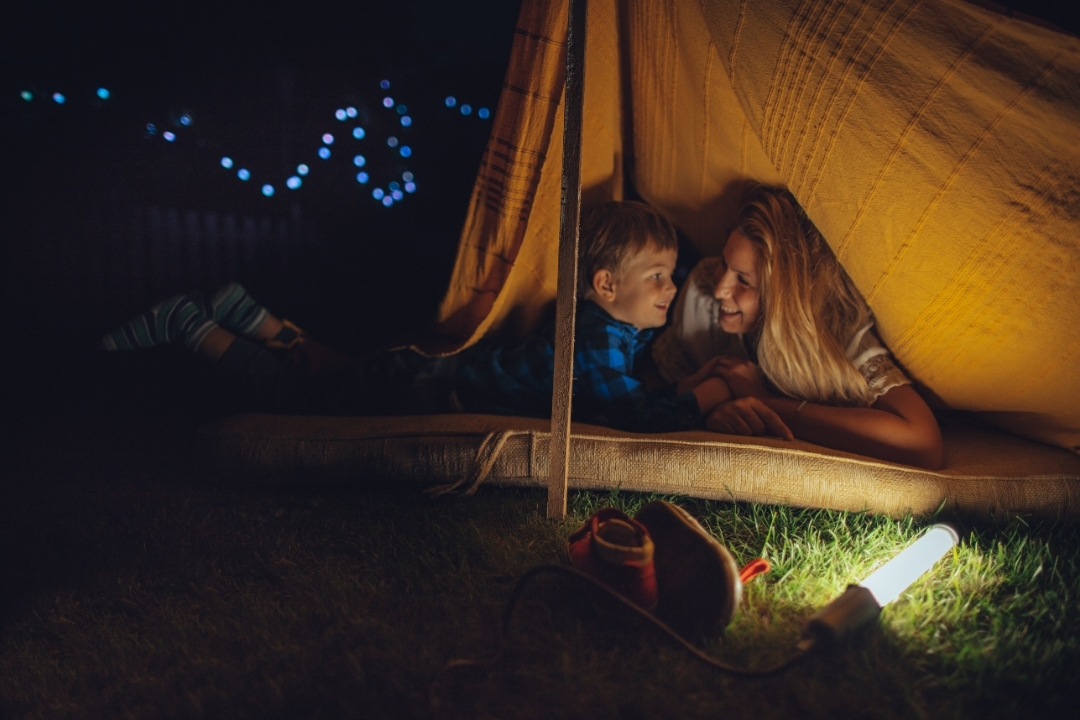 Toddler and mom camping in a tent in the garden