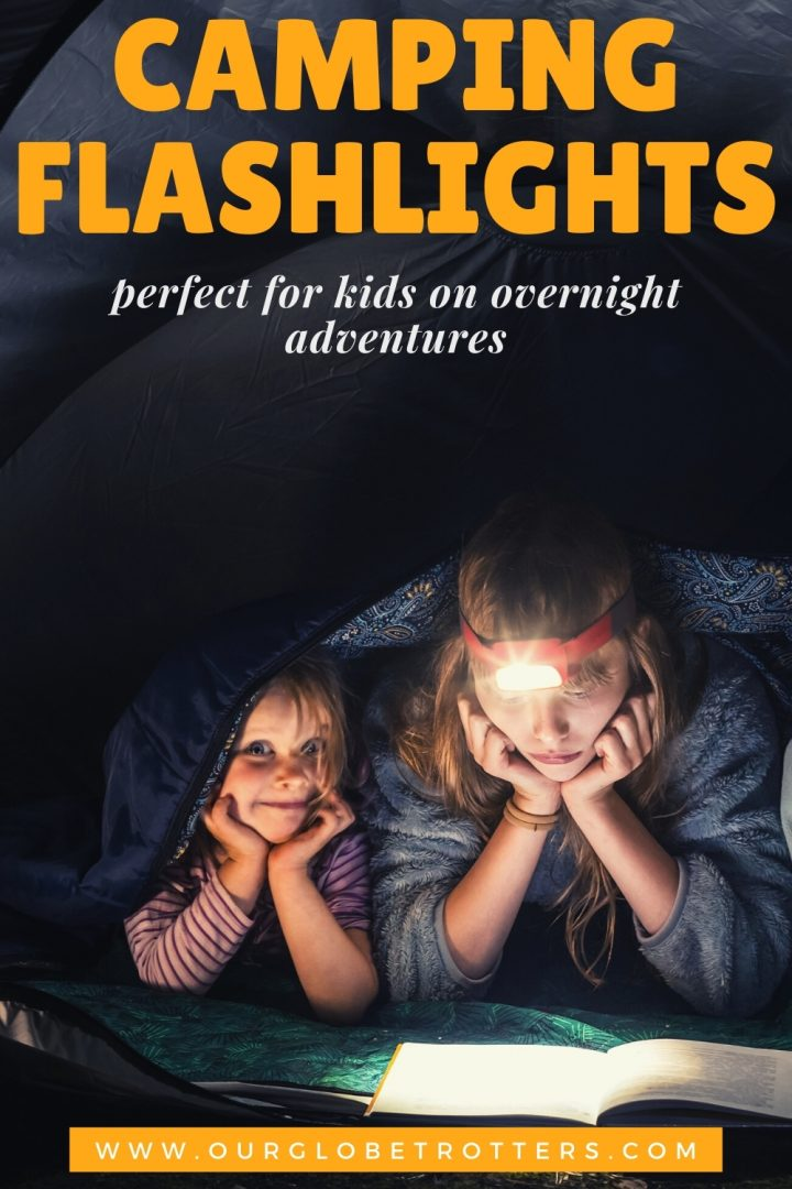 kids reading a book by headtorch light in a tent