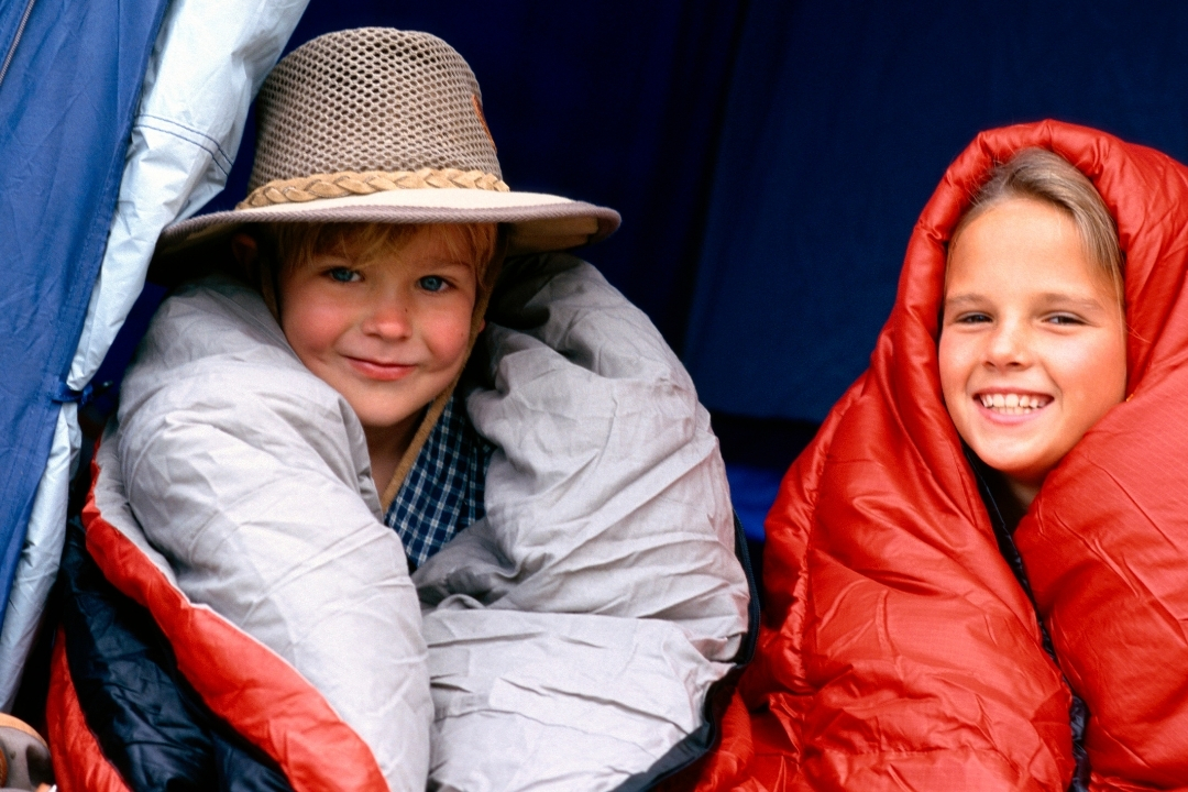Two kids in a tent wrappe up in their sleeping bags