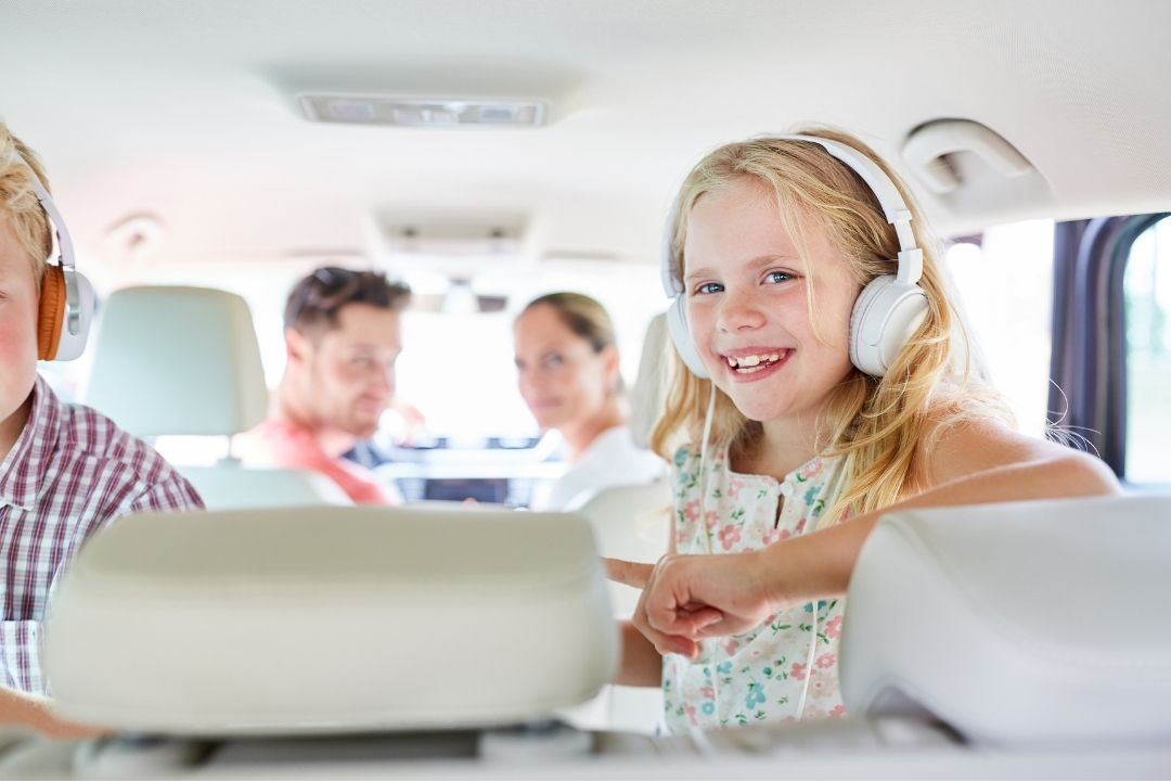 girl listening to headphones in a car