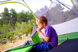 A child sitting in a tent blowing up a camping mat