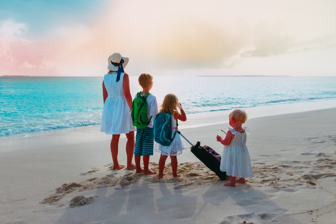 Family standing on a beach wearing backpacks