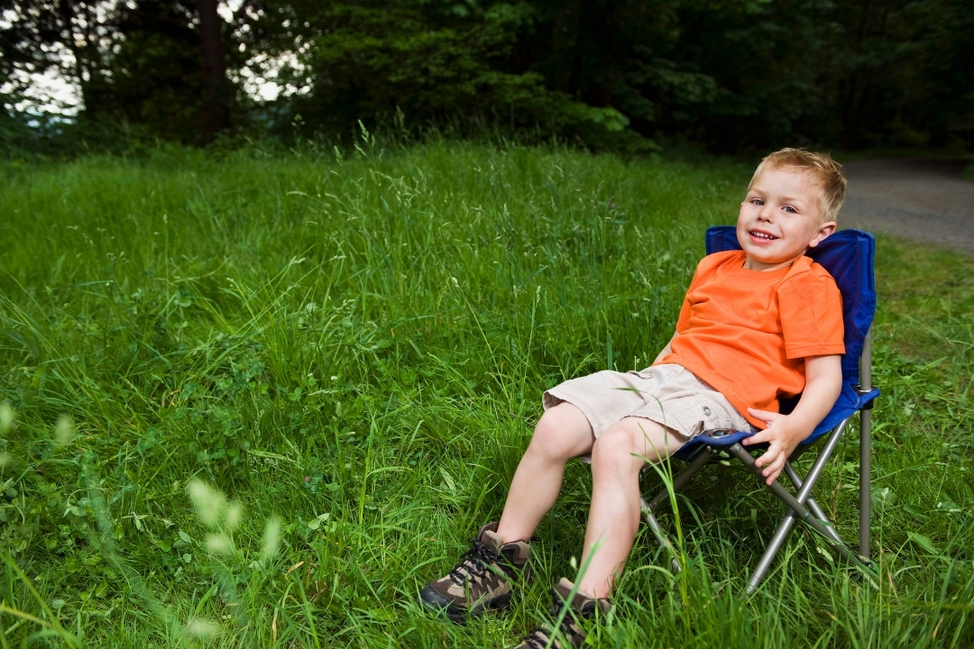 Young boy in a bright orange tshirt sitting in a blue kids camping chair - the best camping chairs for kids