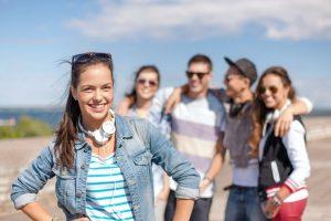 teenager with headphones around her nech, group of teens behind her