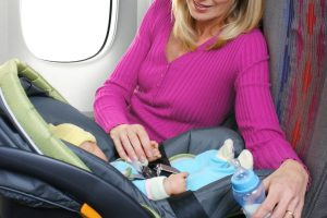 a mother looking after in infant in an car seat onboard an airplane