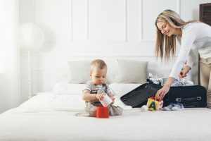 baby playing on bed while mother is packing a suitcase