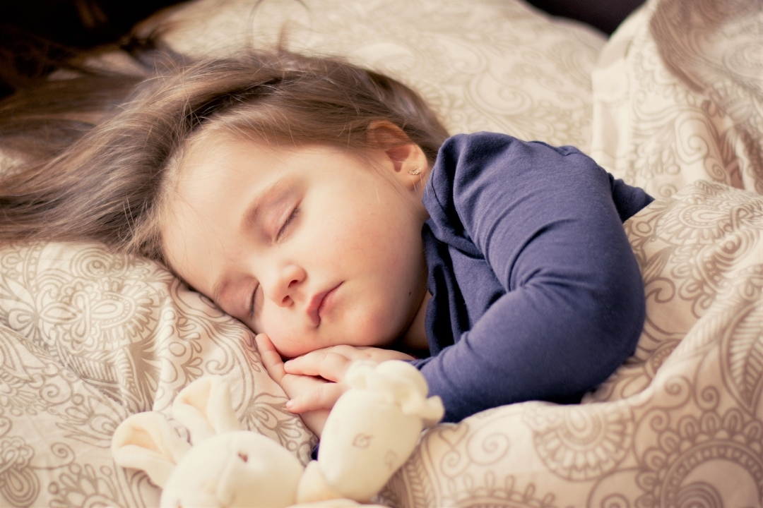 toddler sleeping with a comforter teddy