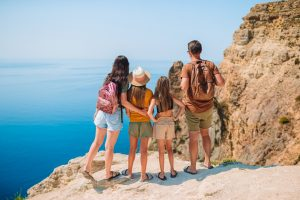 family of 4 looking over a cliff - inspiring travel quotes