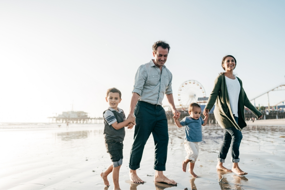 Family walking on beach in california