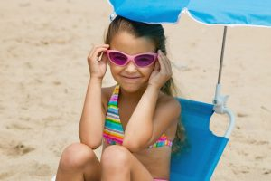 Girl with sunglasses sitting in ablue kids beach chair