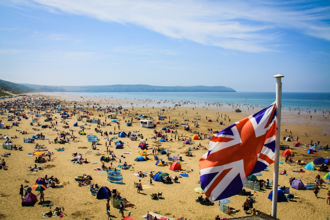 UK Flag flying over a busy English beach in summer - summer staycation ideas