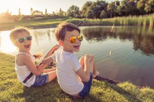two excited children sitting ona river bank with a fishing rod