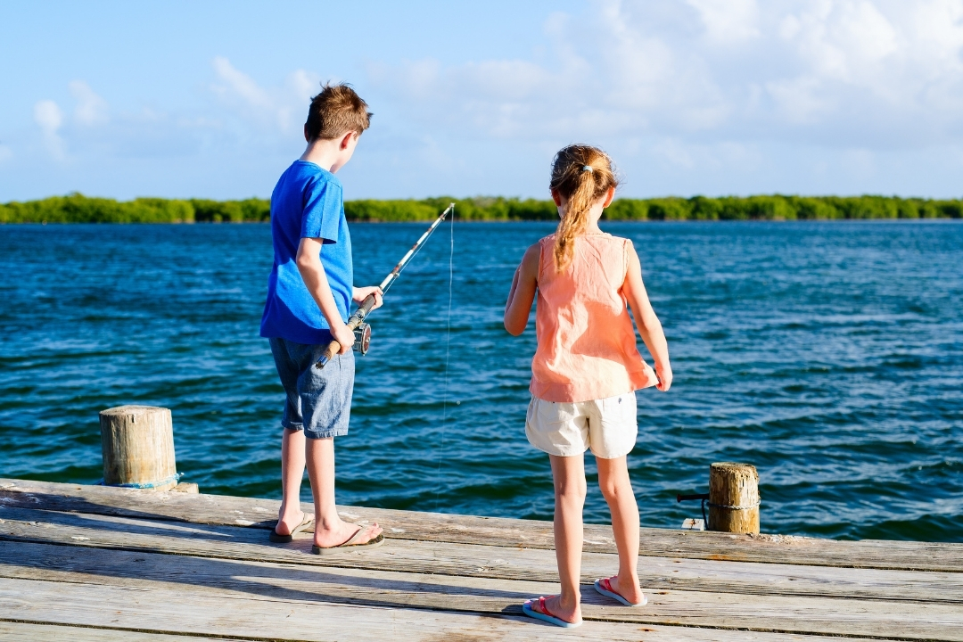 boy and a girl fishing off a pier