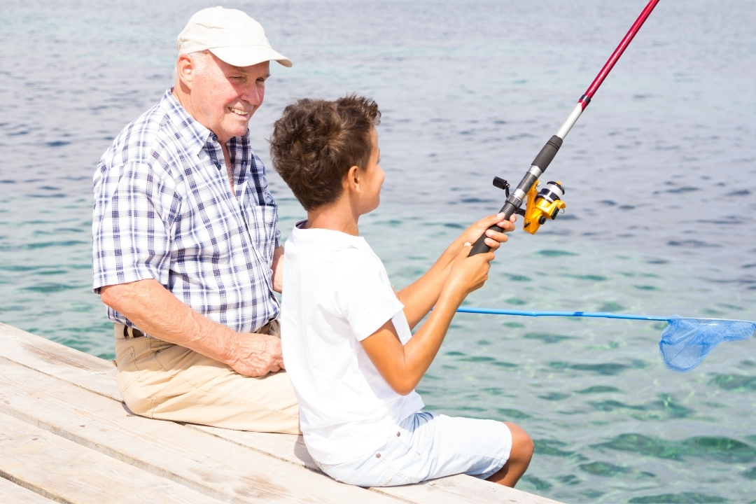 grandfather teaching child to fish