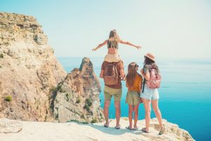 Guest family on a cliff on family vacation looking happy