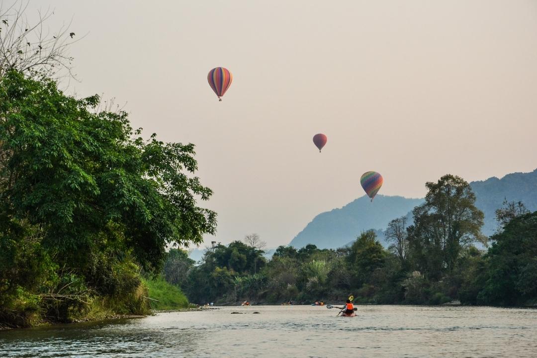 Hot air ballons over river with kayaks Laos