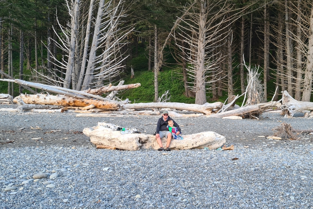 father and son sitting on Rialto Beach Olympic Peninsula