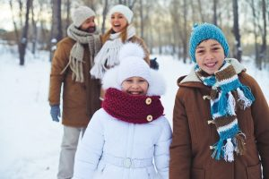 Family of 4 wrapped up in winter coasts in the snow