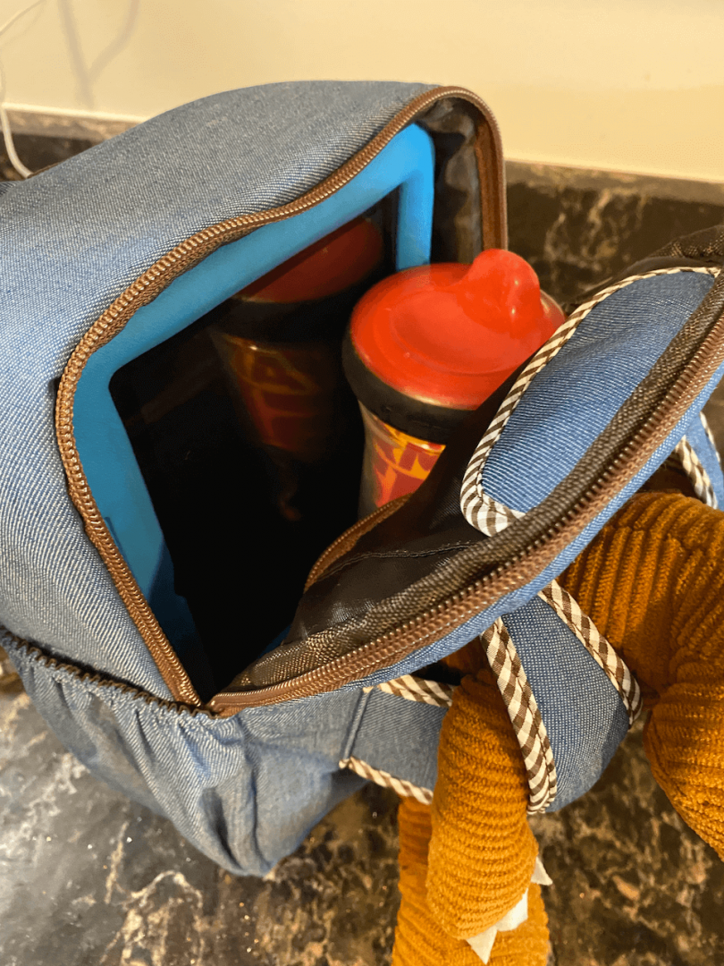 the space inside a naturally kids denim toddler backpack can fit a tablet and a sippy