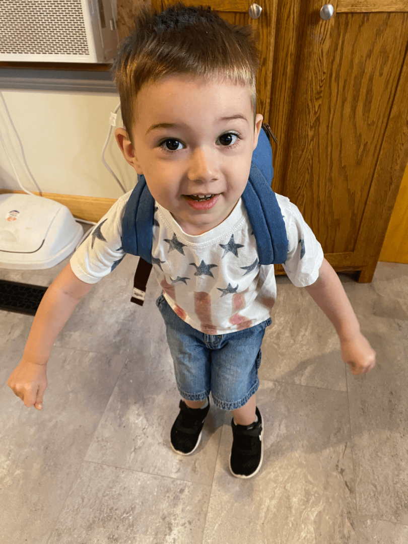 Cute toddler wearing a dinosaur backpack
