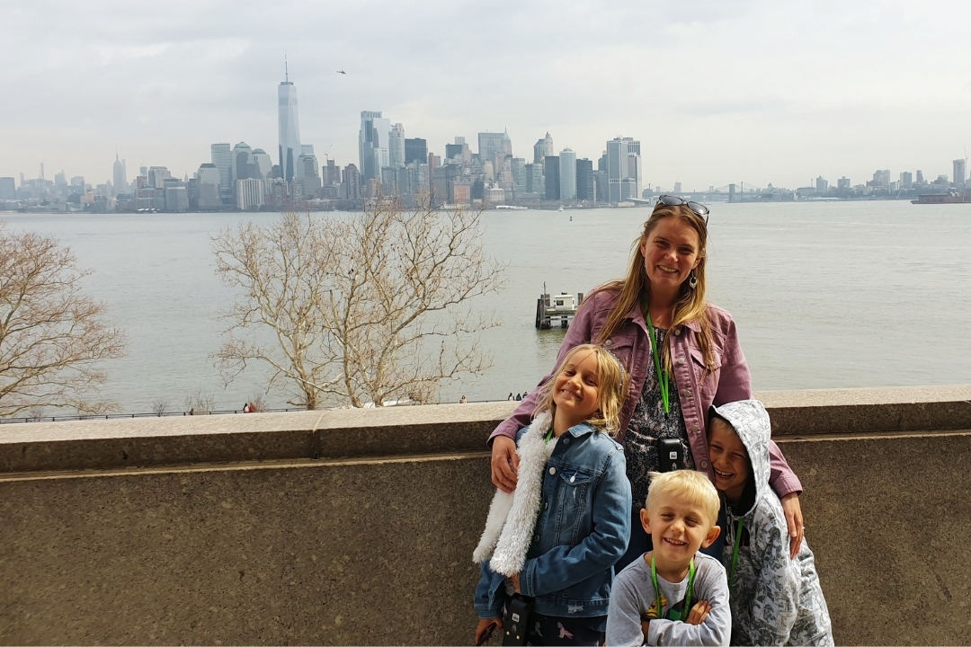 Family on Ellis Island looking back to the New York skyline