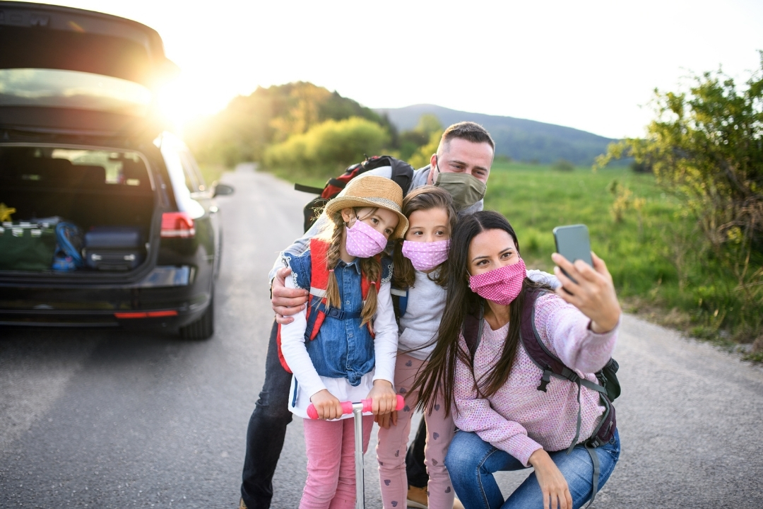 A family of 4 wearing tehir face masks on a road trip taking a selfie