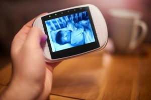 ladies hand looking at a baby asleep in a crib through a portable baby monitor