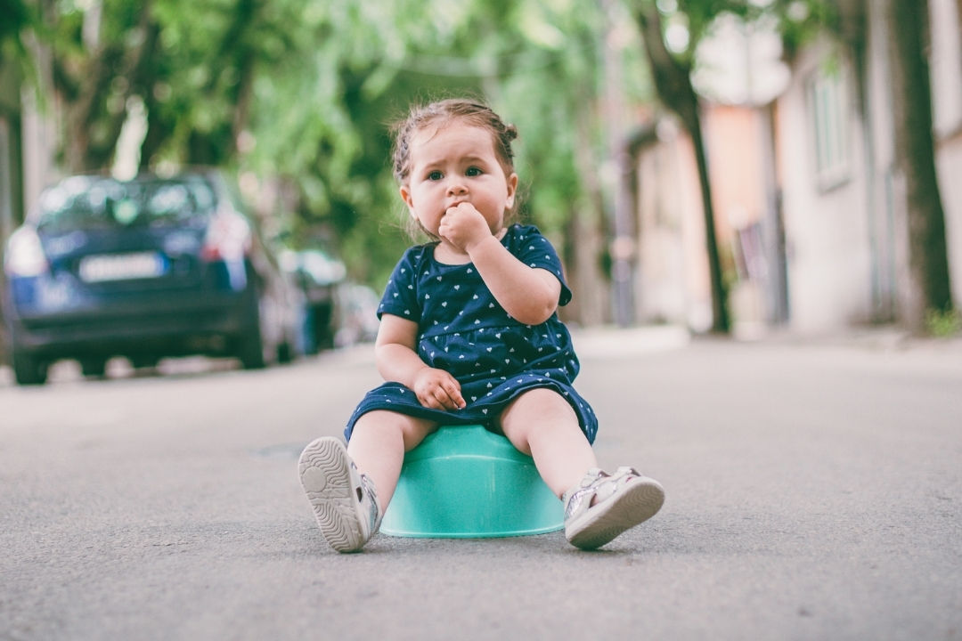 Toddler sitting on potty in the street - travel potty guide