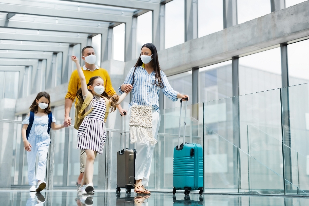 Family in an airport with suitcases wearing face masks