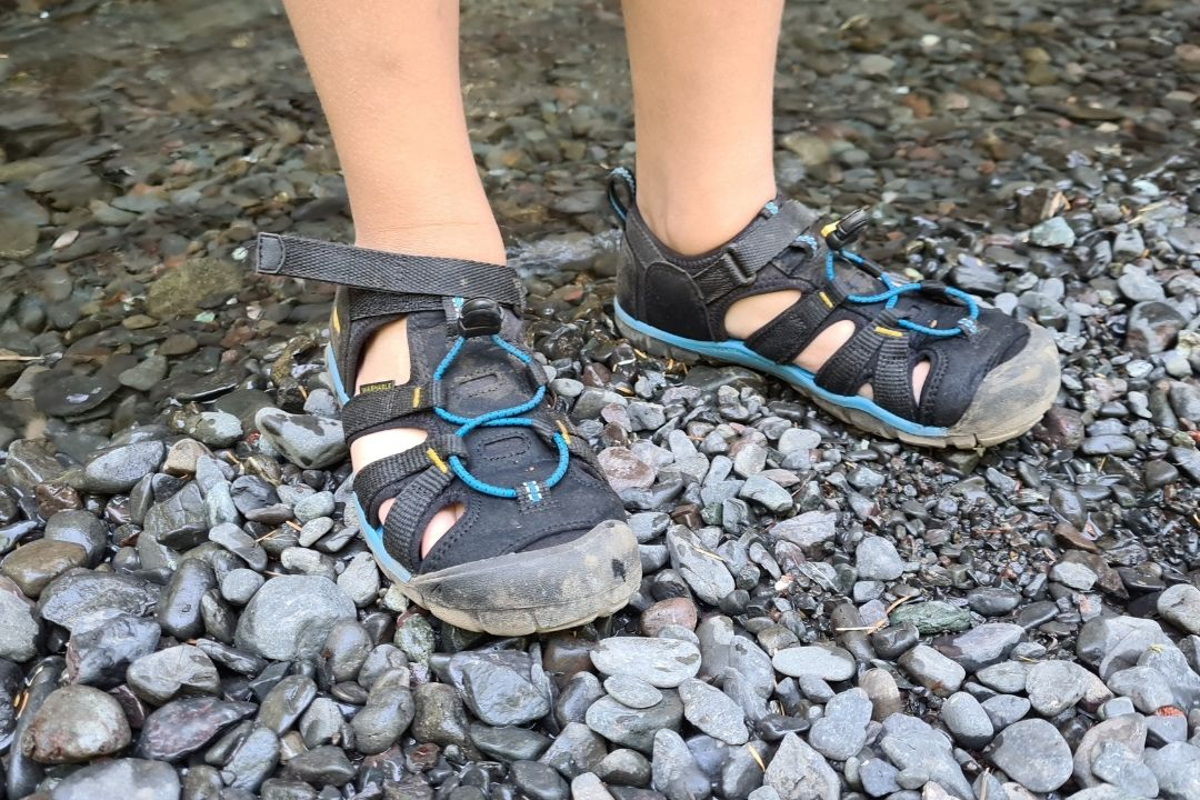 a childs hiking sandal standing in a stream